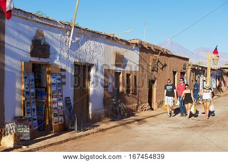 SAN PEDRO DE ATACAMA, CHILE - OCTOBER 23, 2013: Unidentified tourists walk by the street of the town of San Pedro de Atacama, Chile.