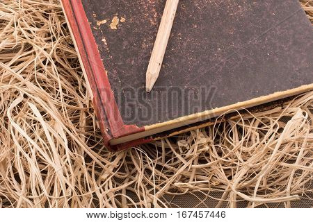 Pencil on a book on a straw background