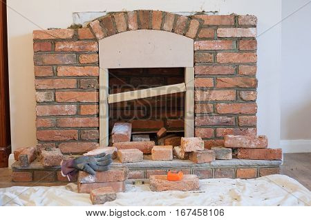 Indoor DIY project: building fireplace in the house: laying bricks template for the arch selective focus