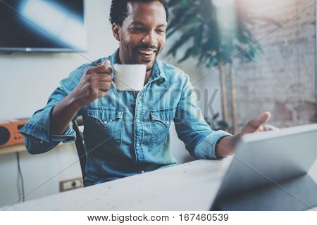 Smiling young African man making video conversation via digital tablet with partners while drinking black coffee in sunny office.Concept of happy business people.Blurred background, film effect