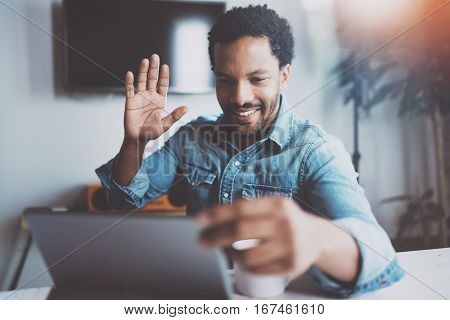 Smiling young African man making video conversation via digital tablet with business partners and greets them hand raised.Concept of happy coworking people.Blurred background, flare