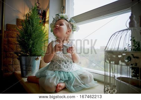 Baby in wreath and dress with tulle and lace sits on the windowsill, and drink of that Cup. Tenderness and feeling of lightness