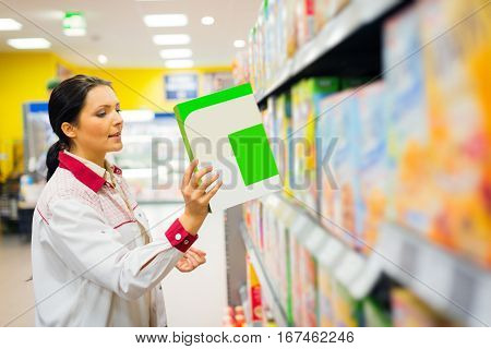 sales clerk refilling shelves at the supermarket