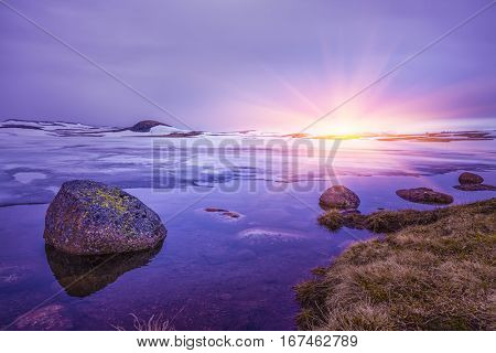Beautiful sunrise over Rocks in a lake, An overcast day at the lake, Winter Landscape, Norway