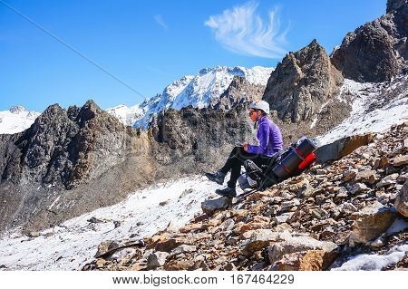 Young female mountaineer in a helmet resting sitting on a backpack and writes the passed route. Against the background of a chain of high rocky mountains and glacier