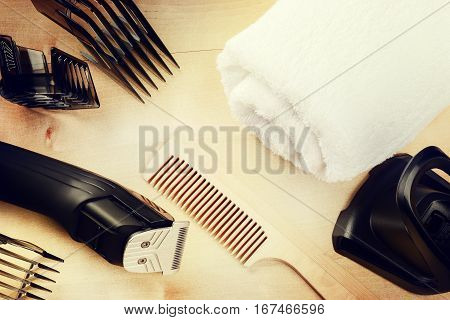 Setting with hair clipper and wooden comb. Beauty and haircare background with copyspace