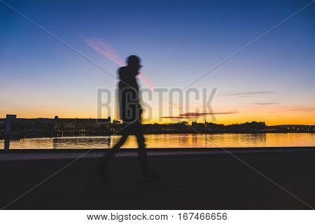 Silhouette of a man walking in Oslo at sunset. Young man walking next to the sea with some city buildings on far background. Travel and time concepts. Long exposure with blurred motion.