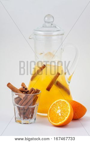 glass decanter with orange juice, cinnamon and ice on a white background
