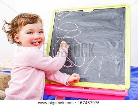 Cheerful beautiful little girl drawing on blackboard