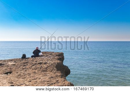 old person fishing in the edge of the ocean on top of sedemenary rock