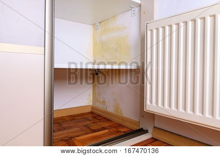Persistent mold on wall in wardrobe and shelves. Hanging heater near the corner.