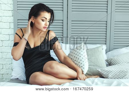 Romantic and sad woman on a bed in the bedroom.