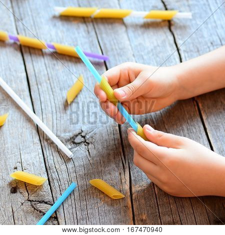 Development of fine motor skills in children. Small child holding a straw and a raw pasta in his hands. Children activity. Simple exercise. Wooden background