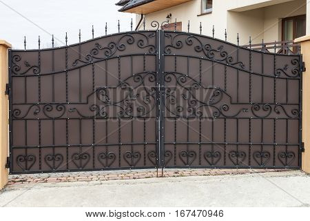 New forged metal double gates for entry of cars into the yard closed