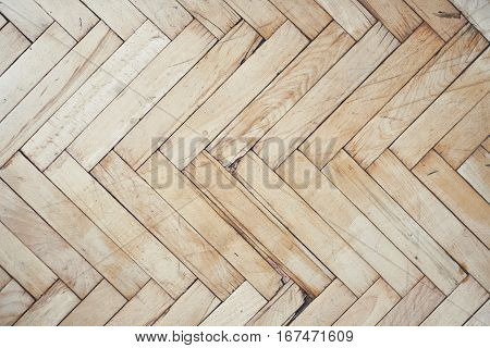 Top view on rich texture of old brushed and distressed wooden parquet floor made from many racks in herringbone pattern