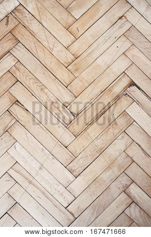 Top view on rich texture of vintage and distressed wooden parquet floor pattern made from many racks in herringbone shape, vertical image
