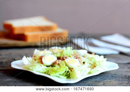 Chinese cabbage salad with canned tuna and quail eggs dressing with olive oil and lemon juice. Cabbage salad on plate, bread slices on wooden table. Simple and quick salad recipe. Closeup