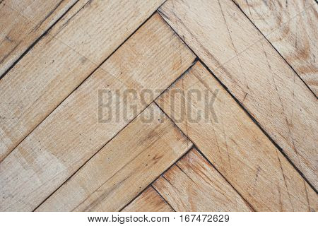 Close top view on vintage parquet floor with geometric mosaic of wood pieces used for decorative effect. Wood block patterns for flooring in herringbone mosaic