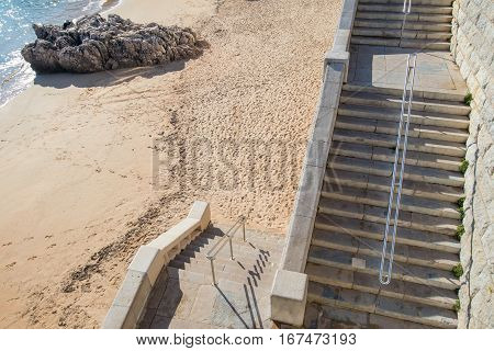 two flights of stairs to access a fine sand beach with a rock just at the edge of the water