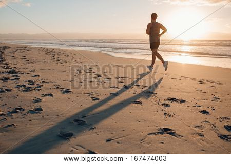 Shot of fit man running along the sea shore in morning. Healthy male jogging on the beach.