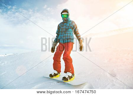 Fully equipped and covered from cold beginner girl snowboarder wears her google mask, stands alone at top of ski slope on backside edge, near ski lift in sun rays, ready to ride down