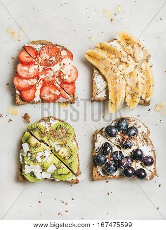 Healthy breakfast toasts. Wholegrain bread slices with cream cheese, various fruit, seeds and nuts. Top view, grey marble background. Clean eating, vegetarian, dieting concept