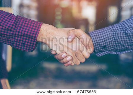 Men shaking hands. Top view of two men shaking hands while standing in coffee shop and restaurant.