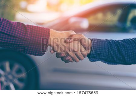 Men shaking hands. Top view of two men shaking hands while standing with car backgroud