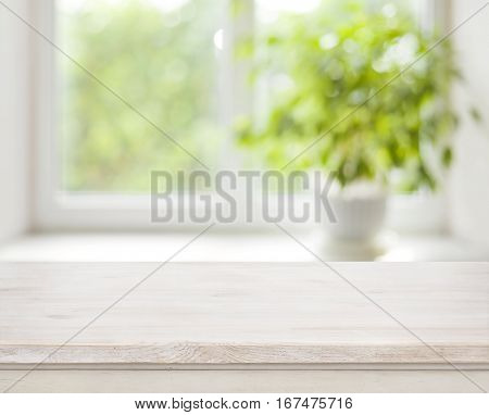 Light wooden table on defocuced spring window background