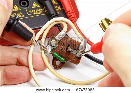 Check vintage resistor with multimeter on a white background