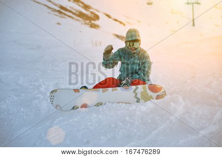 Fallen beginner girl snowboarder wears her google mask, sits alone at traverse of ski slope in sunset rays, smiles and shakes her hand looking at camera, ready to stand up and ride down