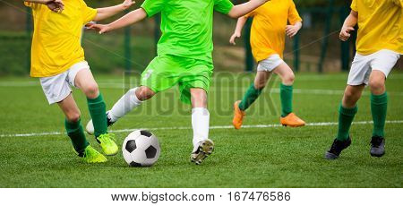 Boys Kicking Soccer Football Game. Running Young Soccer Players. Children Playing Football Match on the Sports Field