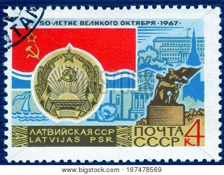USSR - CIRCA 1967: post stamp printed in the USSR shows Coat of Arms, Flag and monument  Latvian SSR, serie