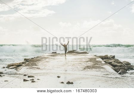 Young woman tourist enjoying waves of stormy Mediterranean sea in winter with raised hands, Alanya, Turlkey