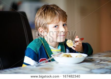 Adorable little school boy eating pasta indoor. Blond child in domestic kitchen or in school canteen Cute kid and healthy food, ravioli or russian pelmeni.
