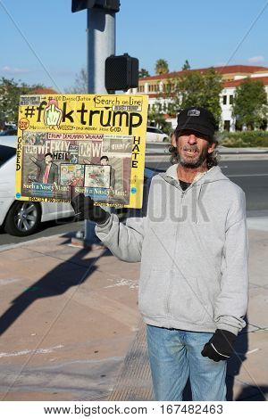 Laguna Hills, CALIFORNIA - JANUARY 26, 2017: A lone protester stands on a street corner with an anti Donald J. Trump sign he made protesting the legitimacy of President Donald J. Trump.