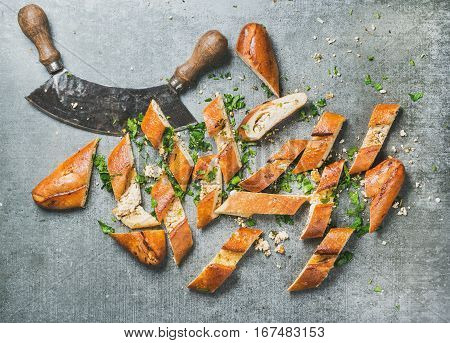 Turkish oriental pizza pide with cheese and spinach cut in slices and chopper on grey stone background, top view, horizontal composition