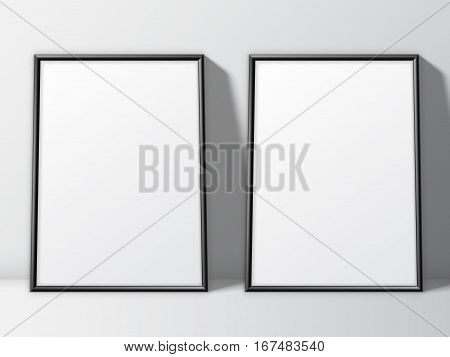 Two blank white posters in thin black frame standing on floor. Poster mock-up template