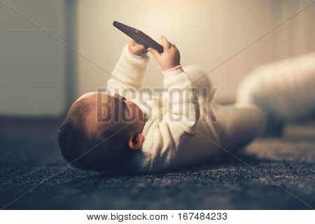 Baby holding smart phone on back at home