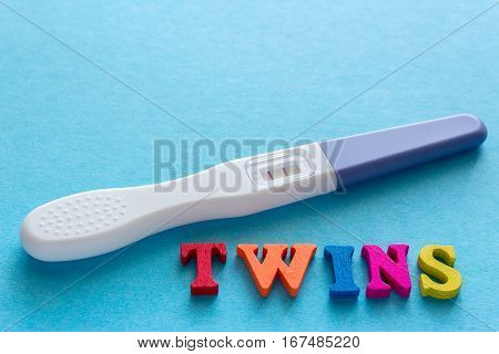 twins word from wooden letters, positive pregnancy test with two stripes on a blue background