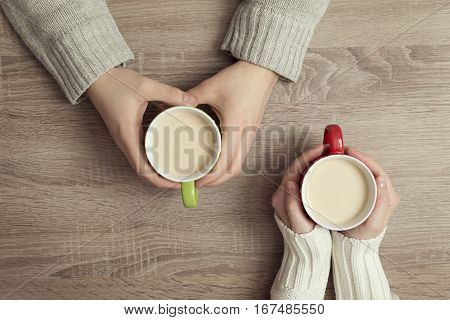Top view of male and female hands holding a cups of coffee on the wooden table