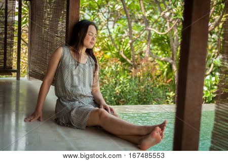 Woman Relaxing On Side Of Private Swimming Pool