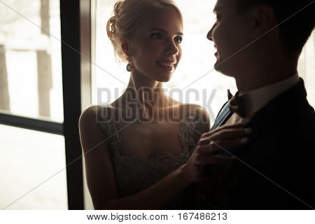 Portrait of smiling bride and groom on window background. Bride is smiling and tenderly looks at groom.