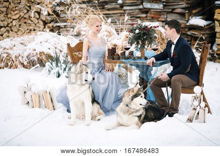 Bride and groom in winter with two dogs malamute sitting at table. On the table are wine goblets candles and bouquet.