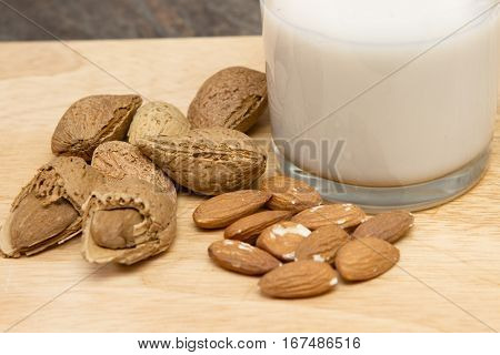 Almond milk A glass of almond milk with almond on a wooden table - vegan milk