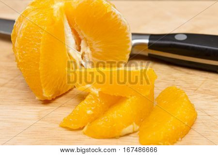 Segmenting and orange Orange segments cut on a wooden board