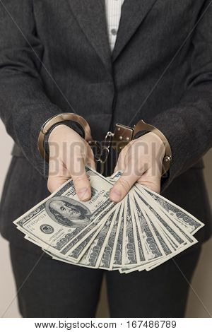 Business woman in a suit with handcuffs arrested offering bribery money for her releasing. Selective focus