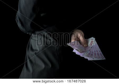 Businessman holding 500 euro banknotes behind his back conceptual of bribe graft or corruption cropped closeup with copy space.