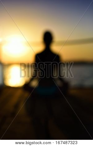 blurred image back woman sitting in a lotus pose on the wooden planks sunset vertical