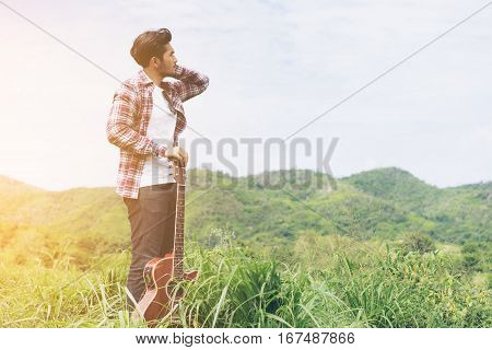 Young Man Holding Guitar In Mountain View